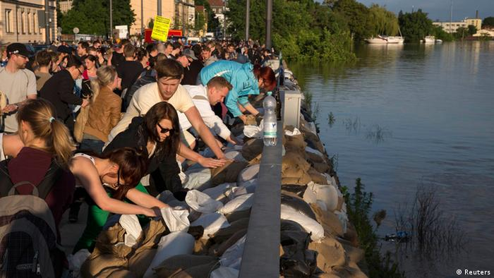 Volunteers pile sandbags to build an embankment fortification in an effort to contain the rising Elbe River at Leipziger Street in the east German city of Dresden, June 5, 2013. Tens of thousands of Germans, Hungarians and Czechs were evacuated from their homes on Wednesday as soldiers raced to pile up sandbags to hold back rising waters in the region's worst floods in a decade. REUTERS/Thomas Peter (GERMANY - Tags: DISASTER ENVIRONMENT)