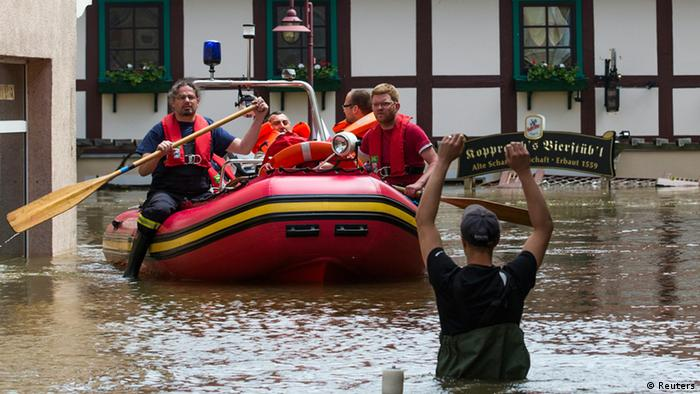 Rescue workers ride a boat in the flooded streets of the east German town of Bad Schandau after the Elbe river has broken its banks (photo: REUTERS/Thomas Peter)