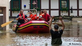 Rescue workers ride a boat in the flooded streets of the east German town of Bad Schandau after the Elbe river has broken its banks, June 5, 2013. REUTERS/Thomas Peter (GERMANY - Tags: DISASTER ENVIRONMENT)