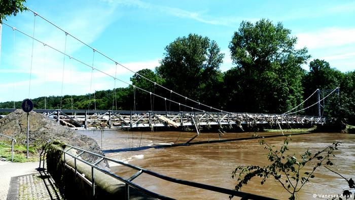 Hängebrücke zeigt eine Hängebrücke, auf die das Hochwasser Äste und Müll gespült hat.