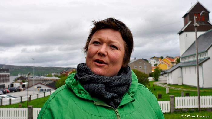 A woman in green looks off camera as she speaks, with the coastal scenery of a small seaside town in the background. (Photo: DW / Lars Bevanger)