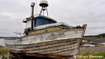 A moldy, disused fishing vessel sits on the ground. (Photo: DW / Lars Bevanger)