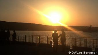 At a very low angle, the bright orange sun backlights a distant peninsula and a pair of men talking on a seaside boardwalk. (Photo: DW / Lars Bevanger)