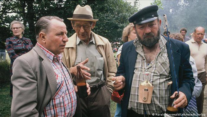 Men enjoying a beer at a horse market in Havelberg in the 1980s, photo by Harald Hauswald
