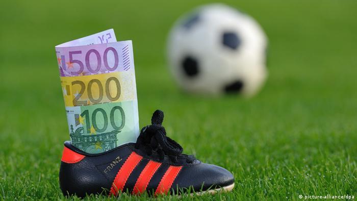 In einem Fußballschuh, der auf einem Rasen steht, stecken mehrere Euro-Geldscheine. (Foto: Uwe Anspach, dpa)