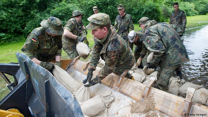 HALLE, GERMANY - JUNE 04: Bundeswehr soldiers stack sandbags to strengthen a dam on the outskirts of the city against the rising Saale river on June 4, 2013 in Halle, Germany. Heavy rains have pounded southern and eastern Germany, causing wide-spread flooding and ruining crops. In eastern Germany floodwaters are moving north through the Mulde, Saale and Elbe rivers, forcing authorities to evacuate thousands of residents. (Photo by Jens Schlueter/Getty Images)