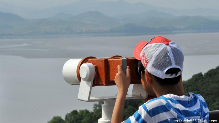 Турист дивиться у бінокль з Південної Кореї на Північну, літо 2013 року