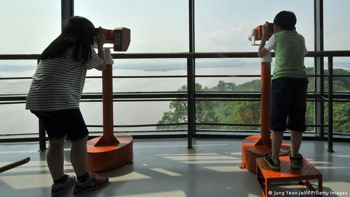 Visitors look through binoculars toward North Korea at a South Korean observation post in the border city of Paju near the Demilitarized Zone (DMZ) dividing the two Koreas on June 6, 2013 (Photo: Jung Yeon-je)
