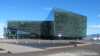 A geometric, modern building covered in green glass (Reykjavík Archiv 2011)
