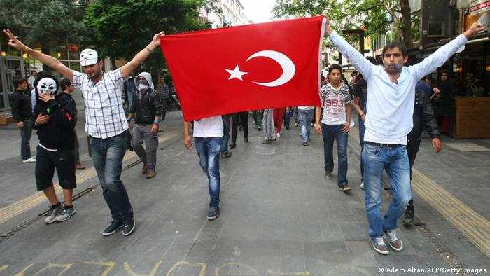 Anti-government protesters hold up a Turkish flag (Photo: ADEM ALTAN/AFP/Getty Images)