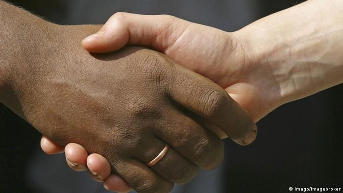 A black and a white hand shaking