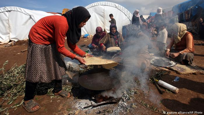 A Syrian refugee makes flat breads (Tanoori) at Atmeh refugee camp, in the northern Syrian province of Idlib, Syria, Tuesday Feb. 19, 2013. Camp administrators say that 16,000 people live here in tents pitched amid olive orchards in northwestern Syria. They are supplied by the Turkish Red Crescent, other international agencies and local benefactors but despite being a few dozen meters from the Turkish border they regularly run short of food, tents, and other amenities. (AP Photo/Hussein Malla) pixel