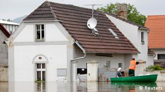 Residents check their flooded house from a boat in the village of Nove Kopisty June 6, 2013. Tens of thousands of Germans, Hungarians and Czechs were evacuated from their homes on Wednesday as soldiers raced to pile up sandbags to hold back rising waters in the region's worst floods in a decade. REUTERS/David W Cerny (CZECH REPUBLIC - Tags: DISASTER ENVIRONMENT)
