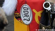 Ostalgie-Souvenirs wie Fahnen mit DDR-Emblem und DDR-Blechschilder werden am 27.11.2012 an einem Verkaufstand am Checkpoint Charlie in Berlin für Touristen zum Verkauf angeboten. Foto: Jens Kalaene/dpa