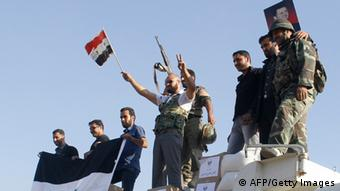 Forces loyal to the Syrian army wave national flags as they celebrate in the main square of Qusair in Syria's central Homs province on June 5, 2013. (Photo: AFP/Getty Images)