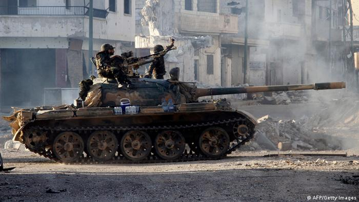 Syrian army troops drive through the ravaged streets of Qusayr in the central Homs province on June 5, 2013, after government forces seized total control of the former rebel stronghold. (Photo: AFP/Getty Images)