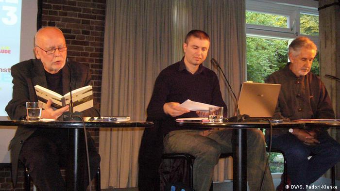 Drei Männer sitzen an Tischen mit Mikrofonen auf einer Bühne. Der Mann, der links sitzt, liest aus einem Buch vor.
