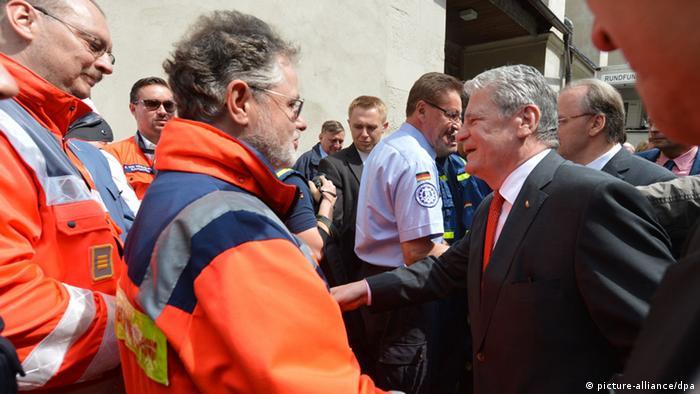 Bundespräsident Joachim Gauck (r) bedankt sich bei Helfern in Halle/Saale (Sachsen-Anhalt) am 09.06.2013 für ihren Einsatz im Hochwassergebiet. Foto: Hendrik Schmidt/dpa