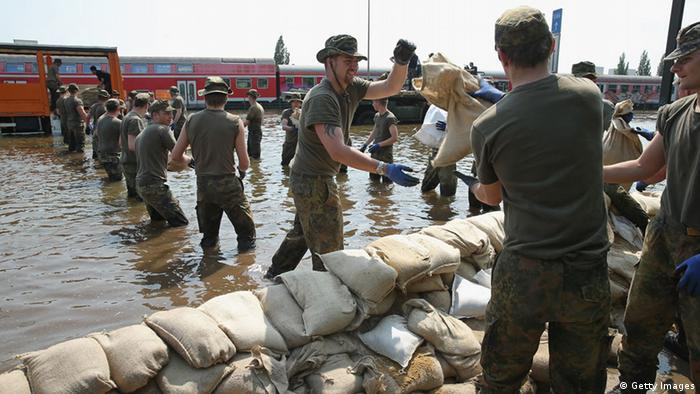 Soldiers of the German Bundeswehr help shore up flood barriers with sandbags against floodwaters (Photo by Sean Gallup/Getty Images)