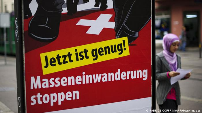 A woman walks past a poster of the far-right Swiss People's Party depicting the legs of men wearing suits marching across the Swiss flag and bearing the slogan That's enough. AFP PHOTO / FABRICE COFFRINI