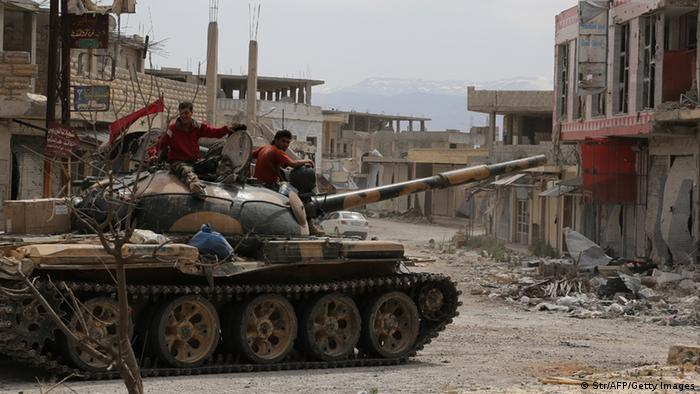 Syrian army soldiers drive a tank in the town of Qusayr, in Syria's central Homs province on June 7, 2013 as regime forces sought to mop up the final pockets of rebel resistance north of Qusayr, after retaking the key town that was an insurgent bastion for a year, a watchdog said. Qusayr's capture gives President Bashar al-Assad the upper hand if a US-Russian plan for the first direct peace talks with his opponents materialises, analysts say. AFP PHOTO / STR (Photo credit should read STR/AFP/Getty Images)