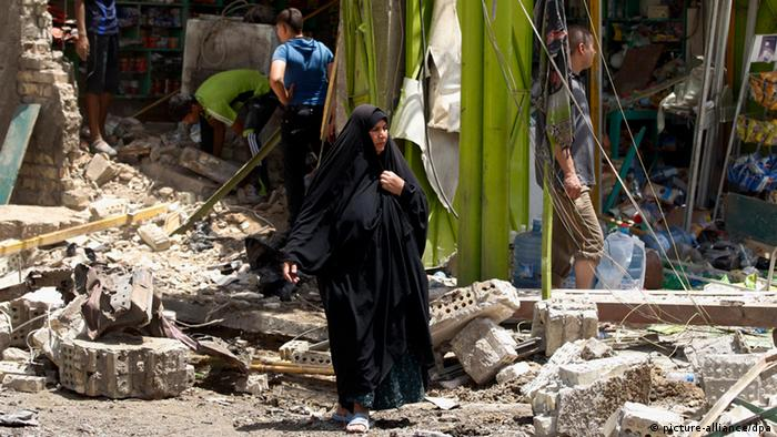Civilians inspect the scene of a car bomb attack at al-Ameen neighborhood in Baghdad, Iraq, Saturday, June 8, 2013. Iraqi authorities say the car bomb explosion has killed and wounded people in a commercial street in the Shiite neighborhood of al-Ameen, southeastern Baghdad. Several shops were damaged in the attack. (AP Photo/Karim Kadim)