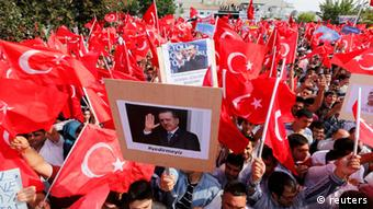 A large group of pro-government supporters hold red Turkish flags in the air. (Photo: Umit Bektas/REUTERS)