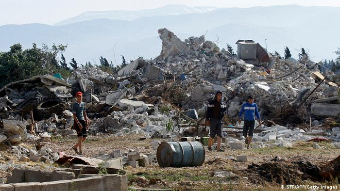 Syrian youths walk amongst the rubble in the village of al-Hamidiyeh, north of Qusayr, in Syria's central Homs province on June 7, 2013 as regime forces sought to mop up the final pockets of rebel resistance north of Qusayr, after retaking the key town that was an insurgent bastion for a year, a watchdog said. Qusayr's capture gives President Bashar al-Assad the upper hand if a US-Russian plan for the first direct peace talks with his opponents materialises, analysts say. AFP PHOTO / STR (Photo credit should read STR/AFP/Getty Images)