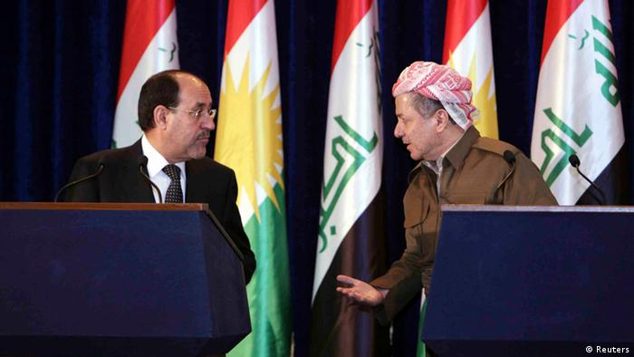 Iraqi Prime Minister Nuri al-Maliki (L) and Iraqi Kurdish President Masoud Barzani (R) speak to each other during a joint news conference in Arbil, about 350 km (220 miles) north of Baghdad June 9, 2013. Maliki visited the Kurdistan region on Sunday for the first time in more than two years, in an attempt to resolve a long-running dispute over oil and land that has strained Iraq's unity to the limit. REUTERS/Azad Lashkari (IRAQ - Tags: POLITICS)