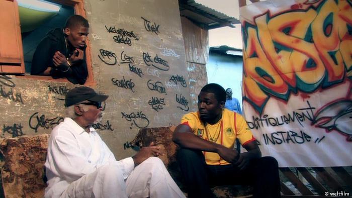 Szene aus Le Président von Jean-Pierre Bekolo. Präsident und rapper vor einer Mauer mit Graffiti (c) weltfilm