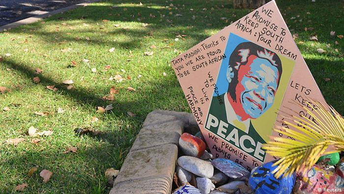 Gardeners clean the lawn as a get well card is placed outside the house of Nelson Mandela in Houghton, June 10, 2013.