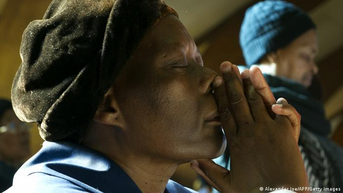 A black South African woman praying for Nelson Mandela (Photo ALEXANDER JOE/AFP/Getty Images)