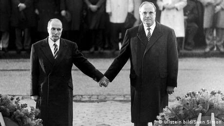 El gesto entre ambos políticos en la localidad francesa de Verdún se comparó a menudo después con el arrodillamiento de Willy Brandt, pero no fue el canciller alemán Kohl quien alargó la mano al presidente francés Mitterand, sino al contrario. El gesto de reconciliación tuvo lugar el 22 de septiembre de 1984 durante un acto conmemorativo en el campo de batalla de Verdún.