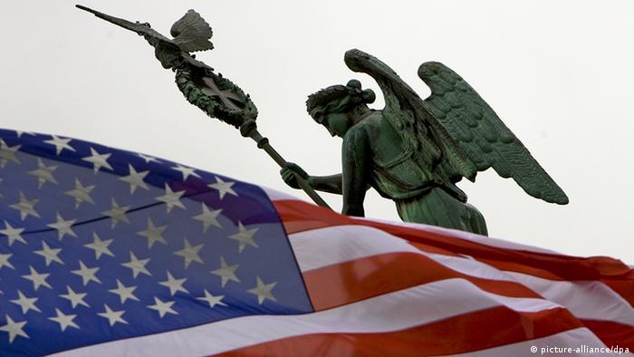 Vor der Quadriga-Figur des Brandenburger Tors in Berlin weht eine US-Fahne - Foto: Arno Burgi (dpa)
