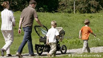 Eltern gehen bei schönem Wetter mit ihren Kindern im Park in Halle/Saale spazieren (Foto: Waltraud Grubitzsch/dpa)