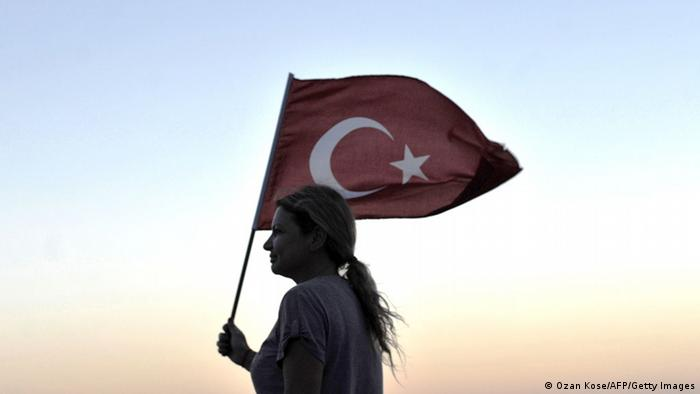 A lone woman holding a Turkish flag Photo: OZAN KOSE/AFP/Getty Images