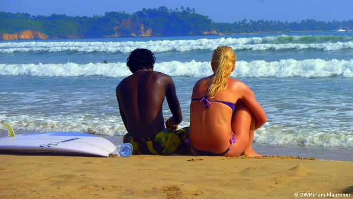 A man sitting next to a woman on a Sri Lankan beach (Photo: DW/Miriam Klaussner)