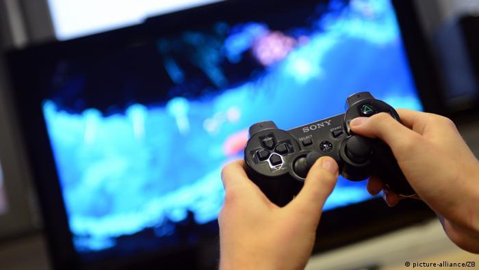 Playstation Videospiel, Hände eines Spielers an der Spielekonsole