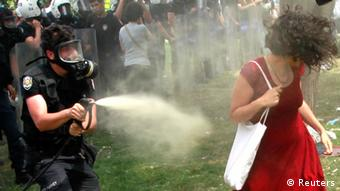A Turkish riot policeman uses tear gas against a woman as people protest against the destruction of trees in a park brought about by a pedestrian project, in Taksim Square in central Istanbul May 28, 2013.In her red cotton summer dress, necklace and white bag slung over her shoulder she might have been floating across the lawn at a garden party; but before her crouches a masked policeman firing teargas spray that sends her long hair billowing upwards. Endlessly shared on social media and replicated as a cartoon on posters and stickers, the image of the woman in red has become the leitmotif for female protesters during days of violent anti-government demonstrations in Istanbul. Picture taken May 28. REUTERS/Osman Orsal (TURKEY - Tags: CIVIL UNREST)