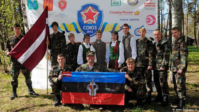 Young ethnic Russians from Lithuania pose for a photo in their military training camp, organised by Russia.