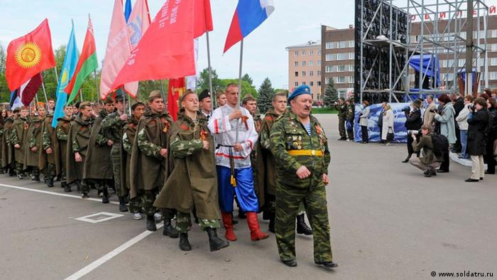 Young people in Russian military uniforms and Russian flags walk in the street (Foto: Gederts Gelzis/DW)