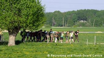 A picture of trees, green fields and young people taking part in a youth training camp. (Photo: Recruiting and Youth Guard Centre, Latvia)