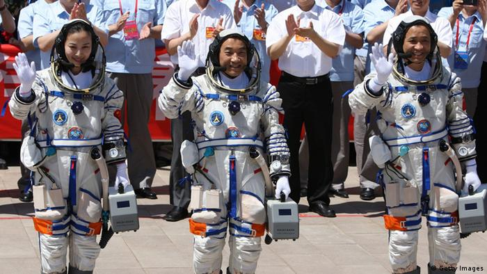 Chinese astronauts (L-R) Wang Yaping, Zhang Xiaoguang and mission commander Nie Haisheng wave to onlookers as they prepare to board the Shenzhou-10 spacecraft in Jiuquan, northwest China's Gansu on June 11, 2013. China was to launch its longest-ever manned space mission on June 11, with its second woman astronaut among the crew, as it steps up its ambitious space programme, a symbol of the country's growing power. CHINA OUT AFP PHOTO (Photo credit should read AFP/AFP/Getty Images)