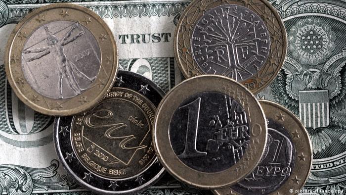 Монеты евро на фоне долларовой купюры