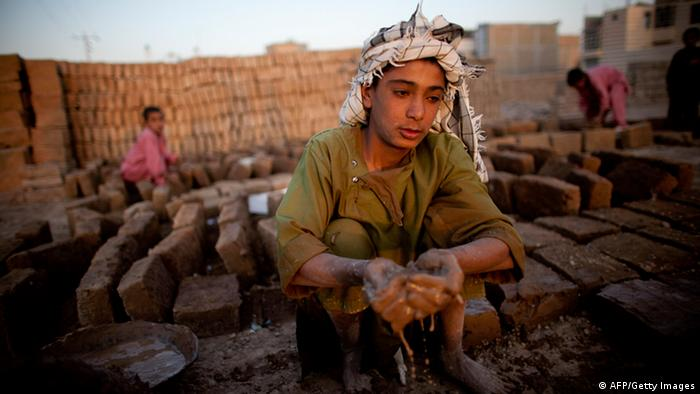Afghan boys work at a factory that makes bricks used for construction September 15, 2010 in Herat, Afghanistan. I(Photo by Majid Saeedi/Getty Images)