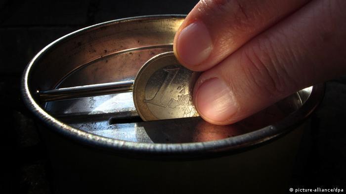 Eine Hand steckt eine Ein-Euro-Münze in eine Geldsammelbüchse (Foto: dpa)