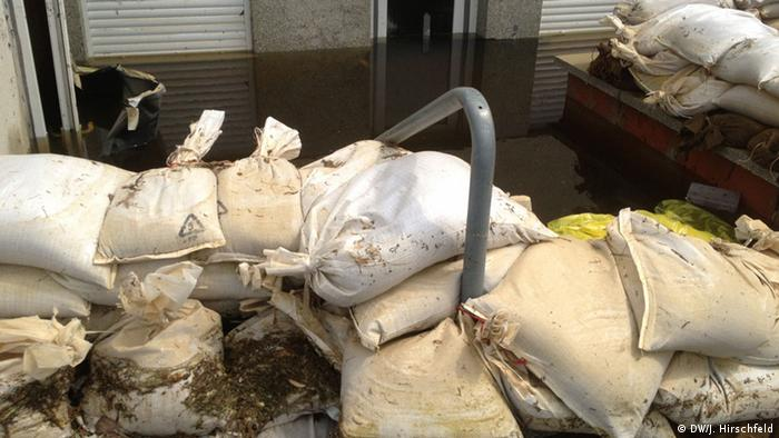 wall of house, water, sandbags Foto: DW / Dan Hirschfeld, 11.6.13