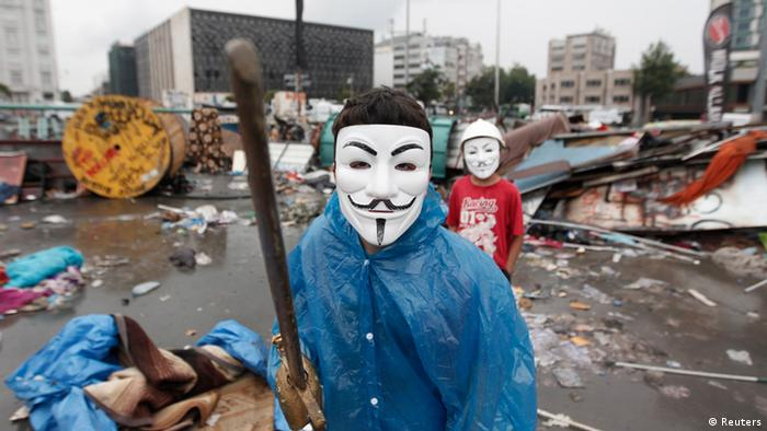 Мальчики, надевшие маски, которые стали символом международного протестного движения