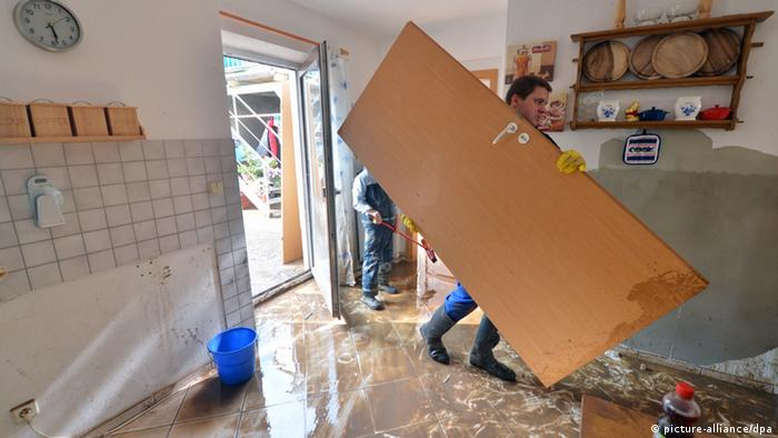 A man carries a door in a flooded home Foto: Hendrik Schmidt/dpa pixel
