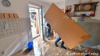 A man carries a door through his recently flooded house Photo: Hendrik Schmidt/dpa